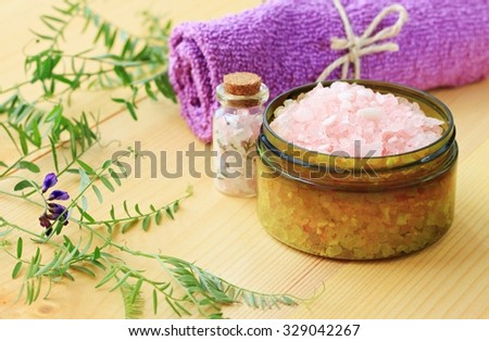 Natural herbal sea salt with aromatic herbs or botanicals - perfect for relaxation. Cosmetic jars and bottles with pink salt, fresh flowers, violet towel, wooden natural background. - stock photo