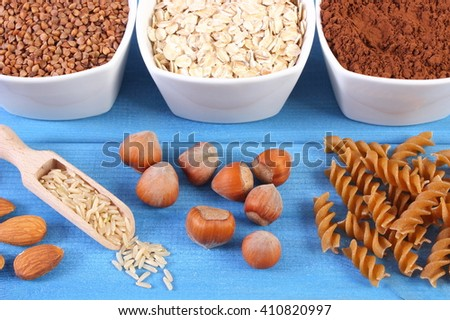 Natural ingredients and products containing magnesium and dietary fiber, healthy food and nutrition, wholemeal pasta, buckwheat, oatmeal, cocoa, brown rice, almonds, hazelnut - stock photo