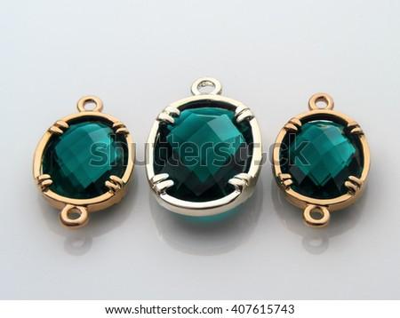 Natural jewelry gemstones green zircon bead in gold on gray. - stock photo