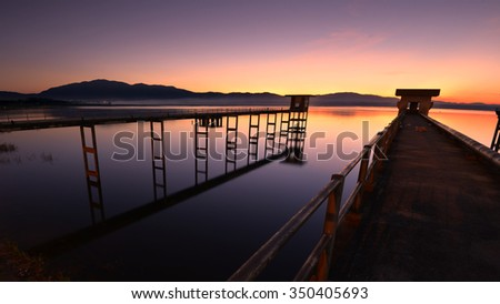Natural landscape view bridge sunrise at Reservoir (Bang-Pra reservoir) in Thailand. - stock photo