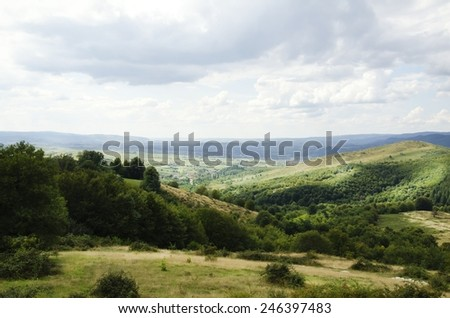 Natural Landscape With Fields and Forests Over Cloudy Sky - stock photo