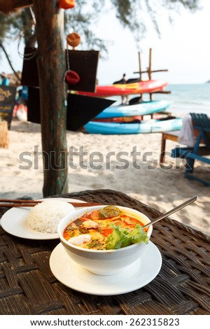 Natural light photo of Tom Yam seafood soup served with rice, shallow DOF seaside view 3 - stock photo