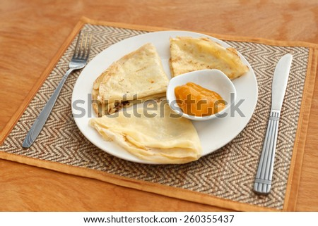 Natural light photo with shallow DOF of crepes with mango jam and tableware on mat and a wooden table - stock photo