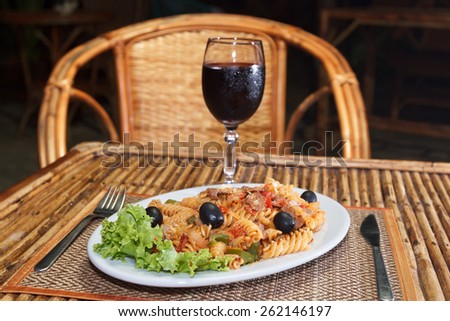 Natural light photo with shallow DOF of macaroni pasta with bolognese sauce and parmesan cheese on a white plate and glass of red wine view 2 - stock photo