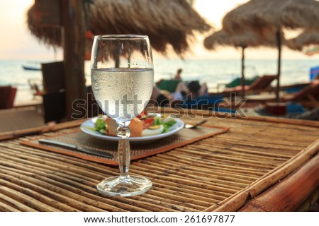 Natural light photo with shallow DOF of romantic beach evening on the sunset with glass of water and dinner horizontal view 1 - stock photo