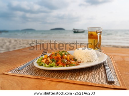 Natural light photo with shallow DOF of stewed seafood with vegetables, steamed rice and beer with sea view background - stock photo