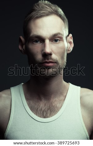 Natural male beauty concept. Close up portrait of handsome charismatic man posing over gray background in white sleeveless underwear. Stylish modern haircut. Studio shot - stock photo
