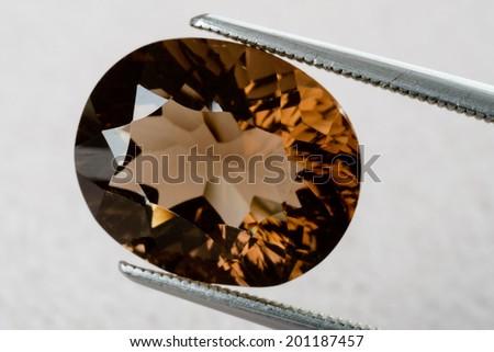 Natural orange brown smoky quartz as oval gemstone. Held by tweezers. - stock photo
