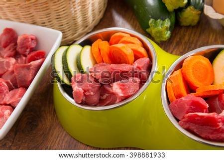 Natural, organic dog's food in a bowl with ingredients zucchini, carrot and raw meat - stock photo