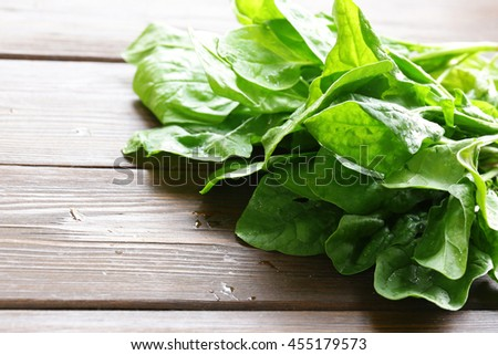 natural organic green spinach on a wooden table - stock photo