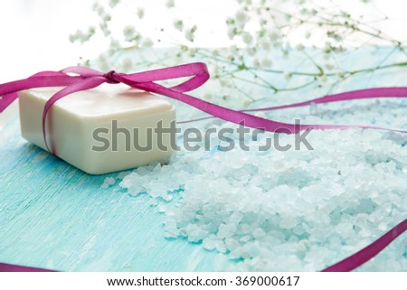 natural organic soap, and sea salt with flowers on a blue wooden table - stock photo