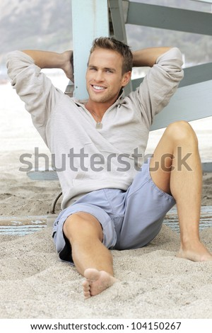 Natural outdoor portrait of great looking young man with big smile leaning in sand - stock photo