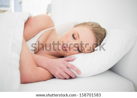 Natural peaceful blonde sleeping in bed in bright bedroom - stock photo