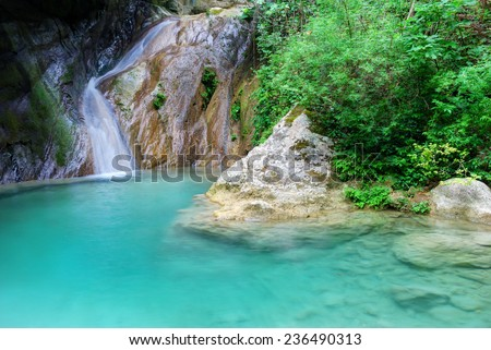 Natural pool with azure water and a small waterfall - stock photo