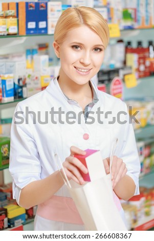 Natural products for beauty care. Vertical shot of a young smiling female pharmacist packing a box copyspace into the paper bag - stock photo