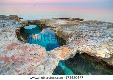 Natural rock bridges over crystal clear blue water on an offshore reef in a tranquil ocean at sunset with a delicate pink tinting the clouds - stock photo