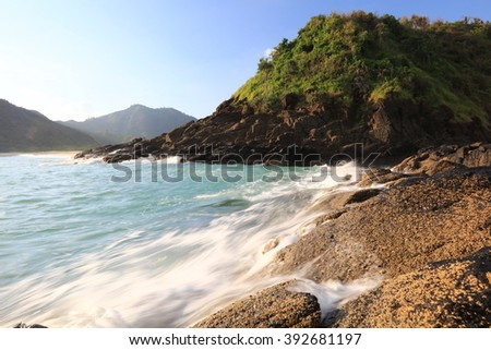 Natural rock with strong water wave and sunset background at Selong Belanak Beach, Lombok, Indonesia - stock photo