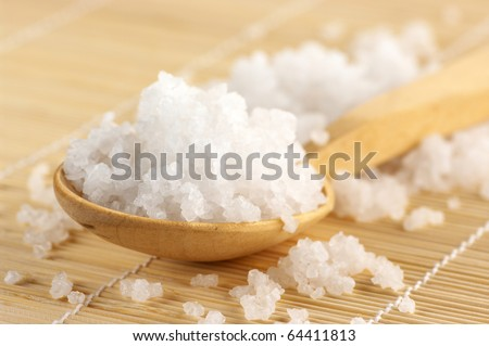 Natural salt of Dead Sea in wooden spoon on mat. Shallow DOF. - stock photo