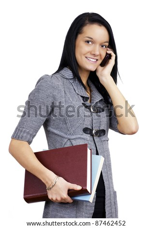 Natural smiling young woman student carrying books and taking on her cell phone isolated over white. - stock photo