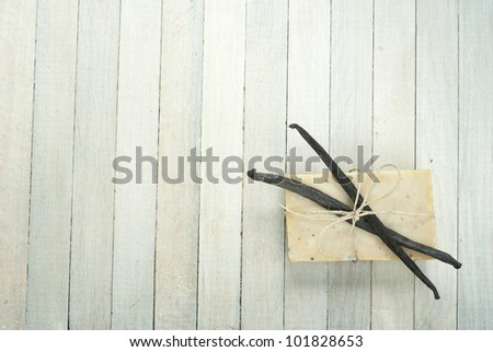 natural soap with vanilla beans on bright wooden background - stock photo
