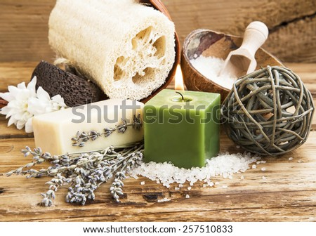Natural Spa and Wellness Products on Wooden Background with Burning Candle,Homemade Soap and Lavender Bouquet, Bath Sponge and Salt - stock photo