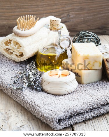 Natural Spa and Wellness Products on Wooden Background with Burning Candle,Homemade Soap and Lavender Bouquet - stock photo