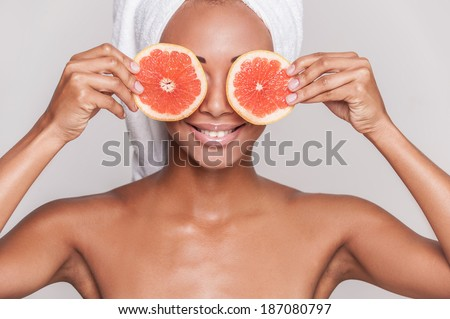 Natural spa. Beautiful young Afro-American shirtless woman holding pieces of orange in front of her eyes while standing isolated on gray background - stock photo