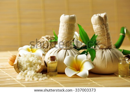Natural spa set with massage balls, salt, aroma oil and frangipani flower with bamboo on wicker background - stock photo