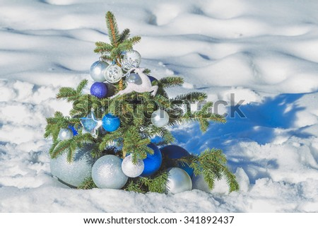 Natural spruce snowy tree decorated with Christmas bright ornaments and baubles of azure and silver - stock photo