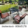 Natural stone pond and wooden patio chair - stock photo