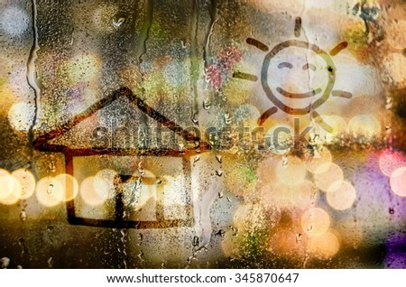 natural water drops on glass window with word house and the sun sign on it - stock photo
