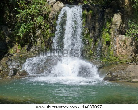 Natural waterfall casdcading over rocks into a calm blue pond below - stock photo