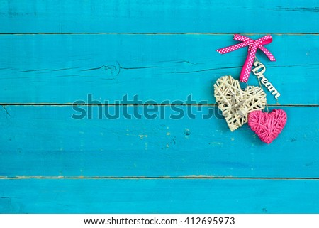 Natural wicker heart, pink rope heart and the word Dream hanging on antique rustic teal blue wood background - stock photo