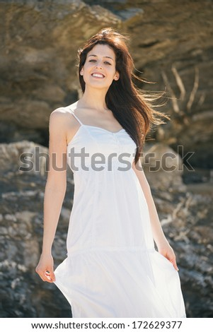 Natural woman summer portrait without makeup. Relaxed brunette female outdoor wearing white dress. - stock photo