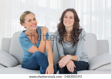 Natural women posing while sitting on the couch looking at camera - stock photo