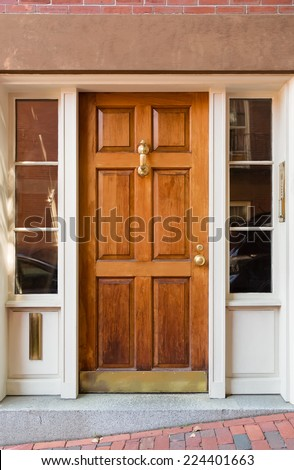 Natural Wood Door with Gold Fixtures and Side WIndows in White Door Frame - stock photo