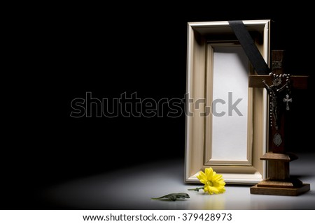 natural wooden mourning frame with crucifix and flower on dark background - stock photo