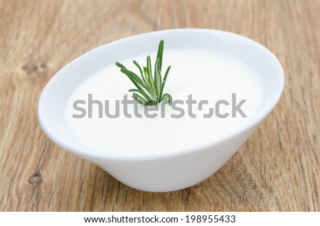 natural yoghurt with a sprig of rosemary on a wooden table - stock photo
