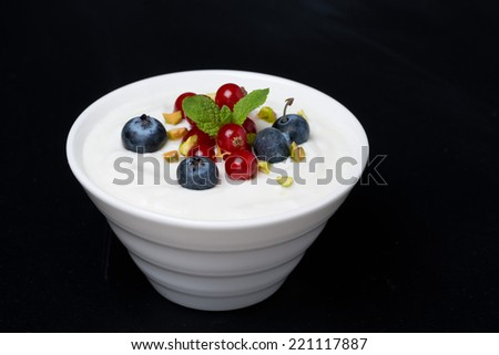 natural yogurt with fresh berries on a black background, close-up - stock photo
