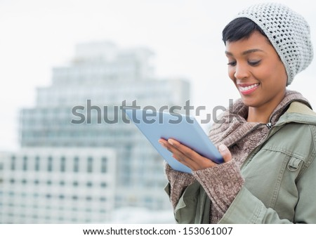 Natural young model in winter clothes using a tablet pc outside on a cloudy day - stock photo