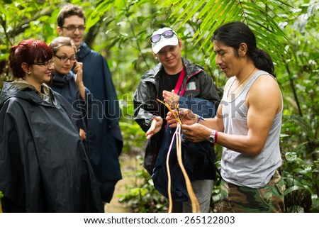 NATURALIST LOCAL GUIDE WITH GROUP OF TOURIST IN CUYABENO WILDLIFE RESERVE, ECUADOR  - stock photo