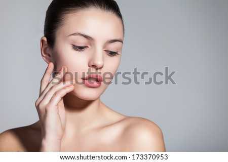 Naturally beautiful brunette woman with flawless skin touching her face dreamily over gray background - stock photo