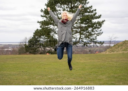 Naturally blond girl with curly hair, jumping outside - stock photo