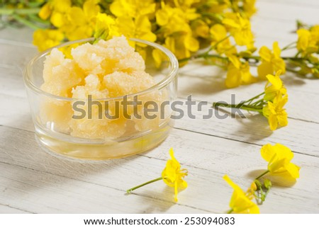 naturally crystallized rape honey with colza flowers on white wooden - stock photo