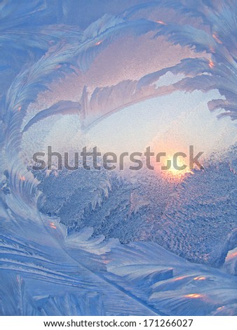 Nature background with ice pattern and sunlight on winter glass - stock photo