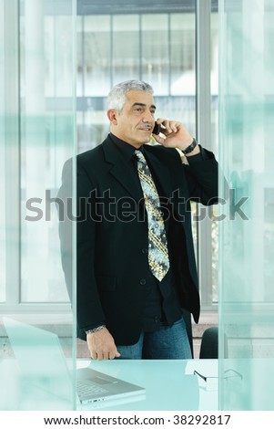 Nature businessman standing behind desk in modern glass office, talking on mobile phone. - stock photo