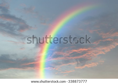 Nature cloudscape with red sky and storm cloud with rainbow - stock photo
