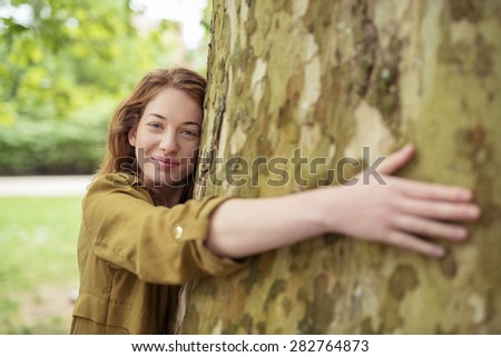 Nature-Lover Blond Teen Girl Hugging Huge Tree Trunk at the Park While Smiling at the Camera. - stock photo
