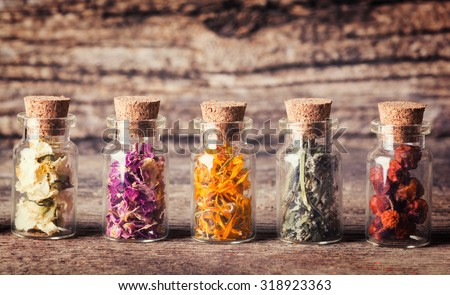 Nature medicine . Herbs in bottles on wooden background . - stock photo