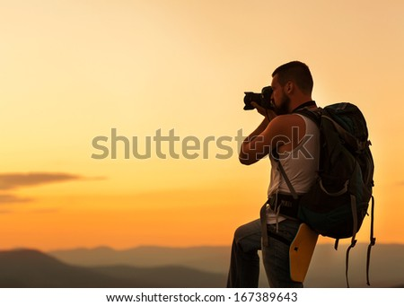 Nature photographer taking photos in the mountains - stock photo